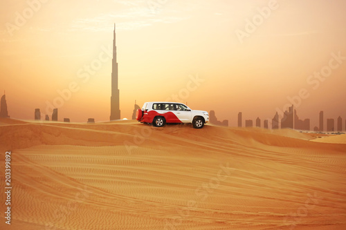 Off-road adventure with SUV in Arabian Desert at sunset with Dubai skyline or cityscape