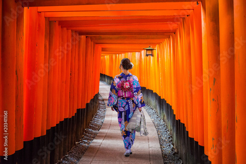 Fotobehang Kyoto Woman in traditional kimono walking at torii gates, Japan