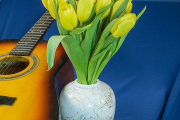 Bouquet of yellow tulips with guitar on blue background