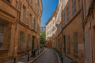 Narrow alley with tall buildings in the shadow in Aix-en-Provence, a pleasant and lively town in the French countryside. Located in Bouches-du-Rhone department, Provence region, southeastern France © Celli07
