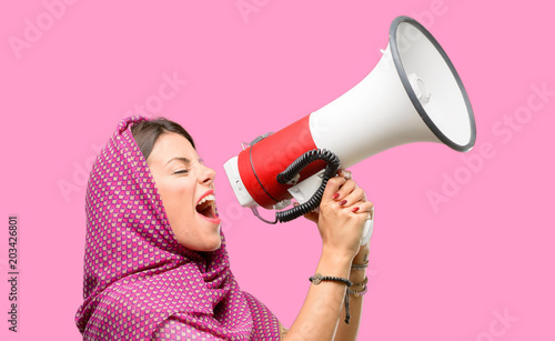 Fotobehang Pop Art Young arab woman wearing hijab communicates shouting loud holding a megaphone, expressing success and positive concept, idea for marketing or sales