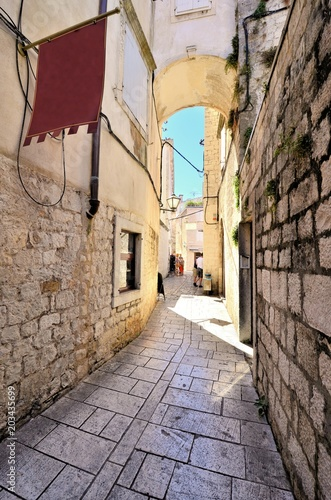 Fototapeta Arched medieval street in the old town of Trogir, Croatia