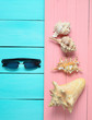 Sunglasses, seashells on blue pink wooden boards.