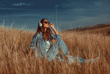 Young woman listens to music and sitting  in the meadow