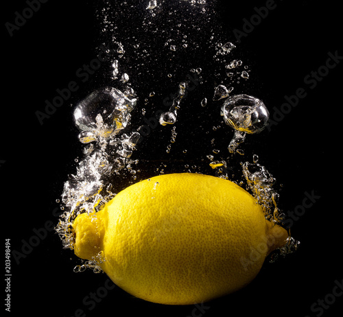 Lemon in water on a black background - 203498494