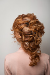 Hairstyle Greek braid on the head of a red hair woman back view close-up on a gray background. © pushann