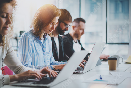 Closeup view of young Coworkers working together on new business presentation at sunny meeting room.Horizontal.Blurred background. - 203512629