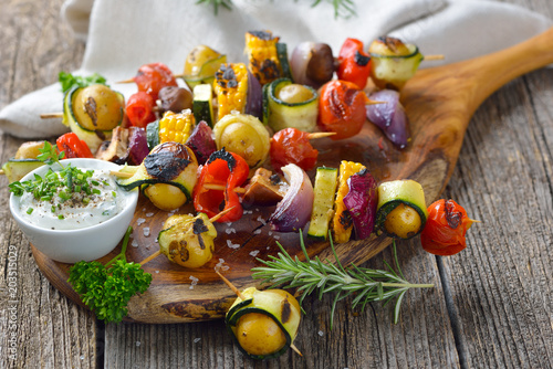 Vegan grillen: Bunte  Gemüsespieße vom Grill mit Kräuterdip  - Grilled skewers with mixed vegetables served  on a wooden cutting board with a vegan herb dip - 203515029