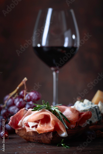 Prosciutto with rosemary and glass of red wine  . - 203520253