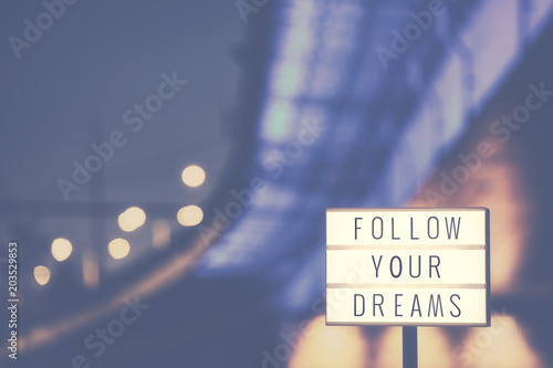 Follow Your Dreams inspirational life quote text in lightbox, city lights in background, color toned picture.