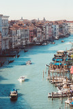 View of the Grand Canal with turquoise water, sailing ships and gandols, houses with red roofs on a bright sunny day in Venice, Italy.