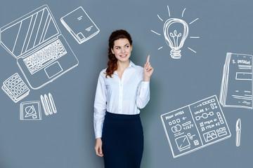 Having an idea. Positive young web developer feeling glad while getting a wonderful idea