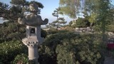 Japanese Garden Stone Lantern 4K UHD. A stone lantern in a japanese garden next to the water. 