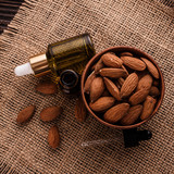 almond essential oil on a wooden background