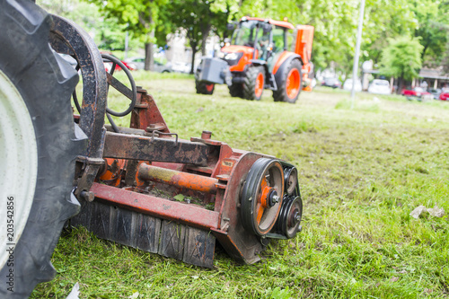 Aluminium Trekker Tractor with lawn mowing grass in a Public Park