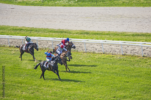 Plexiglas Paarden Galloping race horses and jockeys in racing competition