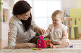 Babysitter and one year old baby playing with toys in nursery