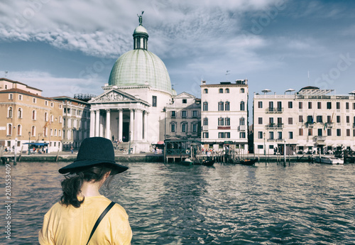 Back view of fashioned traveler woman with hat and yellow t-shirt in Venice - Grand Canal - Italy