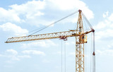 Construction crane against blue sky with clouds.