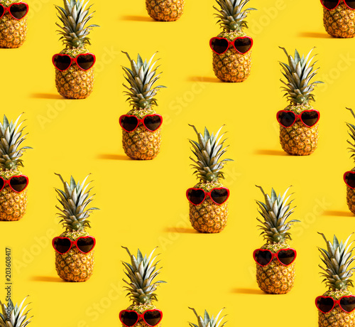 Series of pineapples wearing sunglasses on a yellow background - 203608417