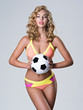 Beautiful sexy woman in  swimsuit holds a soccer ball