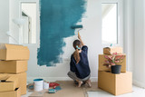 Young asian happy woman painting interior wal