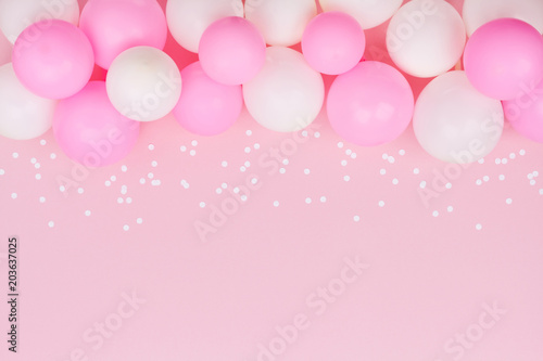 Foto Murales Pastel balloons and white confetti on pink background top view. Flat lay style.