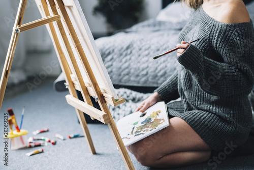 Fototapeta Woman painting on floor of bedroom