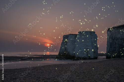 Fotobehang Cappuccino Beautiful colorful sunset over rock stacks on beach with fireflies glowing in a fantasy style image