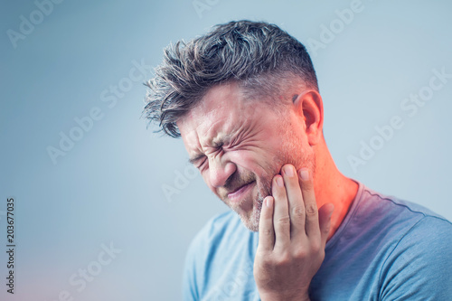 Leinwanddruck Bild Toothache, medicine, health care concept, Teeth Problem, young man suffering from tooth pain, caries