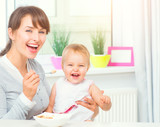 Mother feeding her baby girl with a spoon. Baby food. Healthy smiling family
