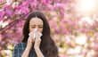 Woman blowing nose because of spring pollen allergy