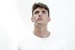 Retrato de hombre joven atractivo mirando hacia arriba con camiseta blanca sobre fondo blanco