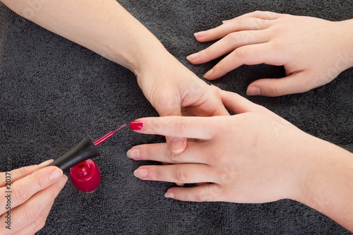 Plexiglas Manicure Close-up of beautician hand filing nails of woman in salon girl painting lady nails