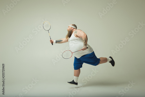 Plexiglas Tennis Cheerful thick guy is playing tennis with excitement. He is running and raising racquet. Copy space