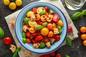 Homemade Panzanella, Tomato traditional Italian salad with red, yellow, orange cherry tomatoes, capers, basil and ciabatta croutons. summer healthy food.