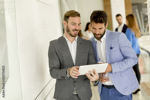 Wall mural Two young businessmen with digital tablet in office