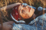 Closeup of young woman listens to music and lying in the meadow - 203764894