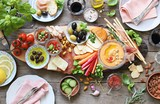 Mediterranean appetizers table concept. Diner table with tapas selection: cured meat and salami, gazpacho soup, jamon, olives, cheese, hummus and vegetables.   Overhead view. - 203766872