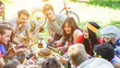 Group of happy friends eating and drinking at picnic dinner on nature