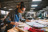 Thoughtful middle-aged industrial female engineer with eyeglasses working with a tape measure in the workshop. - 203780843