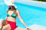 Woman with swimwear and sun hat relaxing at swimming pool