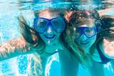 Girl friends diving underwater in resort swimming pool - 203792041