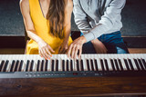 Piano teacher giving lessons to his student in music school  - 203794482