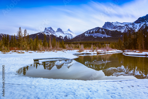 Fotobehang Blauwe hemel Three Sisters Mountain at Canmore, Alberta, Canada. This photo was taken during the transition between winter and snow season.