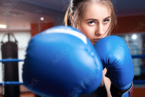 Woman with black boxing wraps and boxing gloves on hands boxing in ring. Active girl fight