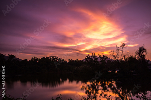 Sunset glow in the sky with reflection from the lake. Amazing natural drawing a beautiful picture in the sky.