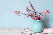 still life with bouquet of blooming cherry branches or sakura in a vase with macarons on blue background