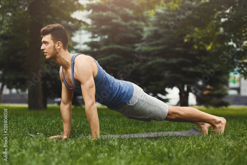 Wall mural Fitness man plank training in park outdoors