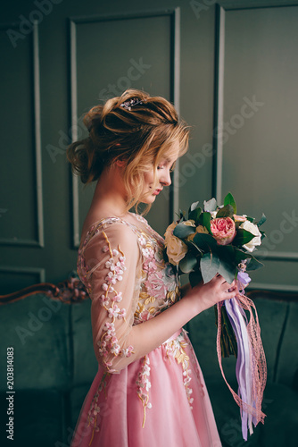 Fototapeta portrait of a young woman in a pink dress holding a bouquet in her hands against a vintage interior background